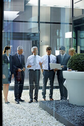 Businesspeople meeting with laptop in an atrium - CHAF000950