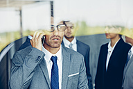 Businessman on cell phone behind window with colleagues in background - CHAF000385