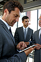 Businessman using digital tablet with colleagues in background - CHAF000389