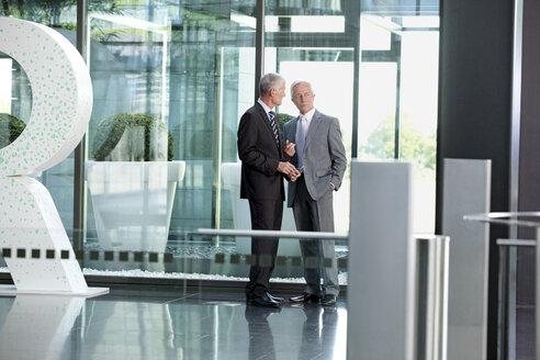 Two businessmen talking in office lobby - CHAF000394