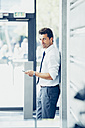 Businessman leaning against a wall holding cell phone - CHAF000398