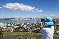 New Zealand, Auckland, New Zealand, Auckland, Tourist photographing Skyline and district Devenport in the foreground - GWF004254
