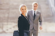 Smiling businesswoman with businessman in background - CHAF000433