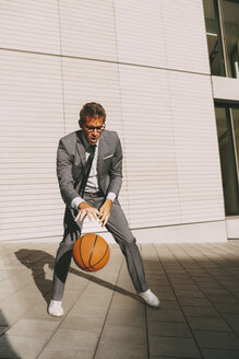 Businessman playing basketball outdoors - CHAF000437