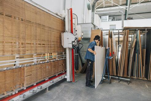 Carpenter in workshop taking wooden board from store - JUBF000023
