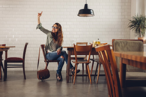 Young woman in restaurant calling for waiter - CHAF001279