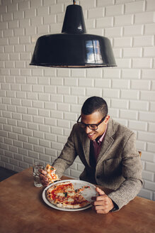 Young man eating pizza in restaurant - CHAF001286