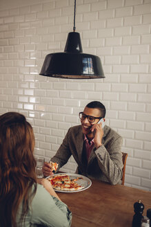 Young couple eating pizza in restaurant, man talking on the phone - CHAF001290
