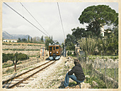 Spain, Islas Baleares, Majorca, young boy sitting next to railway track, train arriving, Tramuntana - MS004680