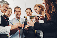 Group of business people raising a toast with champagne at office - CHAF000483