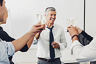 Group of business people raising a toast with champagne at office - CHAF001324