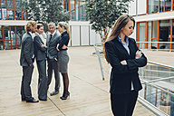 Businesswoman with crossed arms, excluded from group of business people - CHAF000496