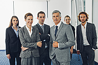 Group of business people standing in office , looking at camera - CHAF000514