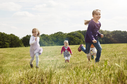 Four little children running on a meadow - STKF001321