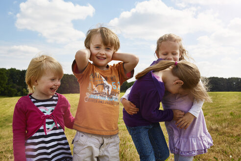 Four little children playing on a meadow - STKF001324
