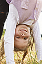 Portrait of happy little girl doing handstand on a meadow - STKF001327