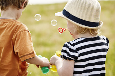 Back view of two little children blowing soap bubbles - STKF001330
