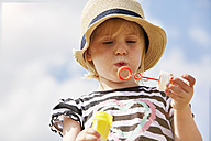 Portrait of little girl trying to blow soap bubbles - STKF001333