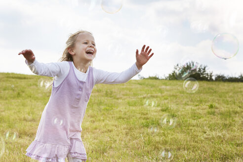 Little girl trying to catch soap bubbles on a meadow - STKF001336