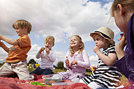 Children sitting on a blanket eating sweets - STKF001345