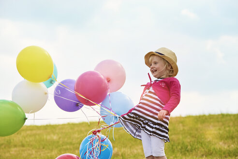 Little girl with balloons on a meadow - STKF001348