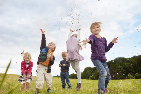 Five little children throwing confetti on a meadow - STKF001357