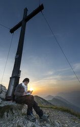 Austria, Tyrol, woman on summit writing in summit book - MKFF000237