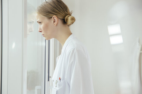 Serious female doctor looking out of window - MFF001835