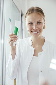 Portrait of smiling female dentist holding toothbrush and toothpaste - MFF001837