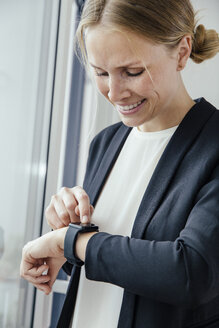 Smiling young businesswoman checking her smart watch - MFF001852