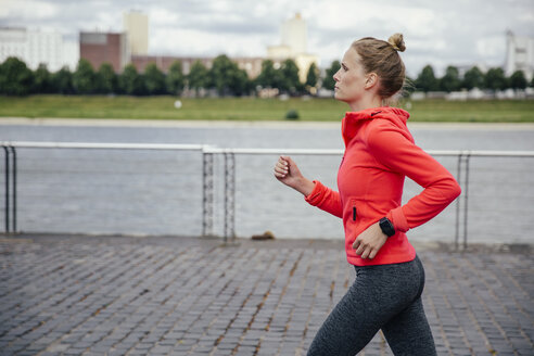 Germany, Cologne, young woman jogging at River Rhine - MFF001859