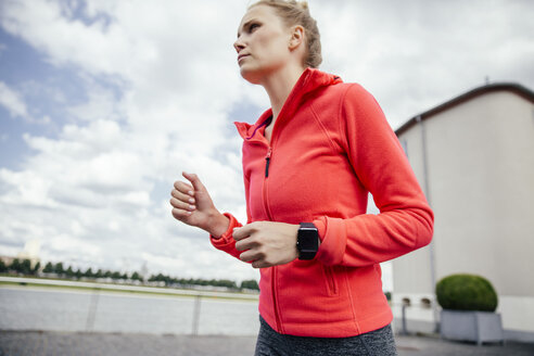 Germany, Cologne, young woman jogging with smart watch - MFF001861
