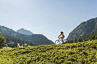 Austria, Tyrol, Tannheim Valley, young woman on mountain bike in alpine landscape - UUF004931