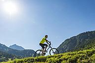 Austria, Tyrol, Tannheim Valley, young man on mountain bike in alpine landscape - UUF004933