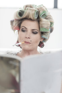 Portrait of woman with hair curlers and magazine smoking a cigarette - ZEF006298