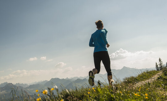 Austria, Tyrol, Tannheim Valley, young man jogging in mountains - UUF004969