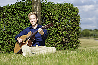 Smiling young man playing guitar in meadow - GDF000796