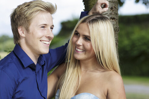 Smiling young couple at tree - GDF000798