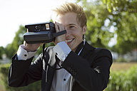 Smiling young man outdoors taking picture with polaroid camera - GDF000802