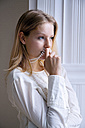 Blond young woman with pearl necklace thinking - CHAF000561