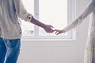 Mid-section of couple standing hand in hand at the window - CHAF000566