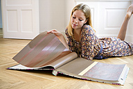 Young woman lying on floor selecting wallpaper from a catalogue - CHAF000568