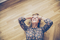 Top view of young woman lying on floor holding her head in pain - CHAF000572