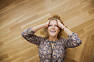 Top view of smiling young woman lying on floor holding her head - CHAF000574