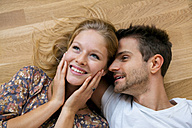 Top view of smiling young couple lying on floor - CHAF000576