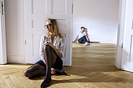Pensive young woman in empty apartment with man in background - CHAF000578