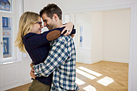Happy young couple hugging in empty apartment - CHAF001007