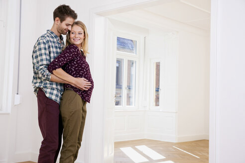 Young man embracing pregnant woman in new home - CHAF000588