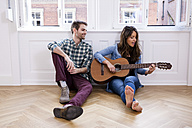 Young couple sitting on floor with woman playing guitar - CHAF000603