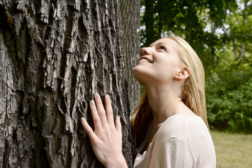 Young woman leaning on tree trunk - BFRF001330